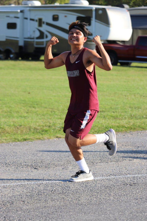 Luis (Freshman) flexing on his competition with a smile during a hard meet.