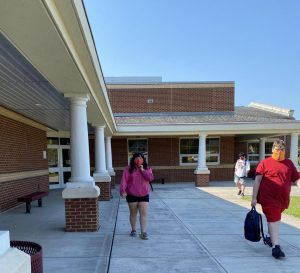 Lillie Laprade and Matthew Lovern head towards their bus after completing their first half day of in person learning.